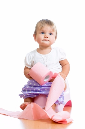 funny baby sitting on chamber pot with toilet paper roll